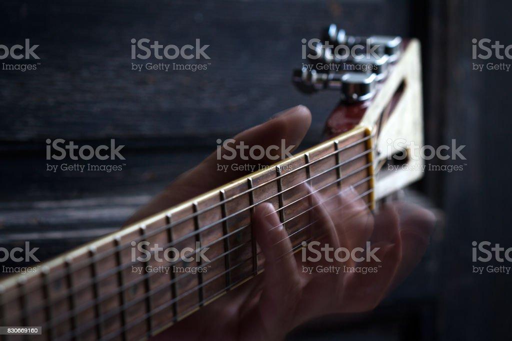 fingers on guitar dark background stock photo