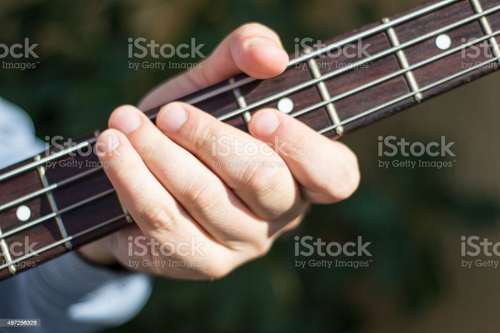 Fingers on the bass guitar strings. Bass player. Guitar and strings. stock photo