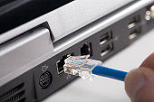 istock Fingers plugging usb cable into back of laptop 172161962