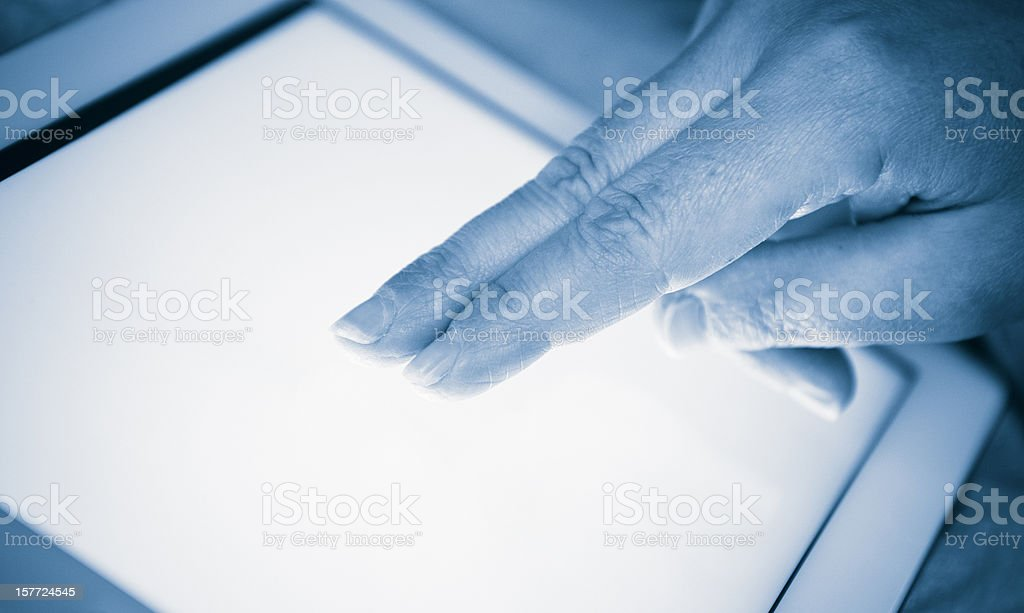 fingers touching the screen of a digital tablet royalty-free stock photo