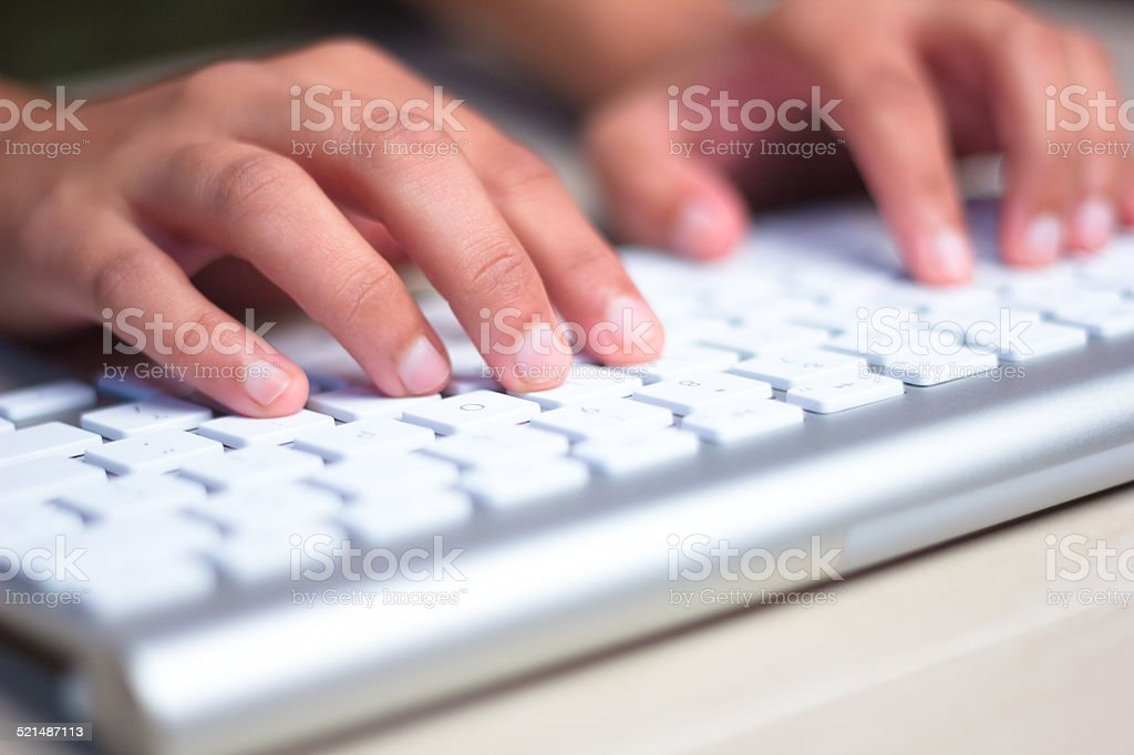 Fingers Typing on keyboard in close-up stock photo