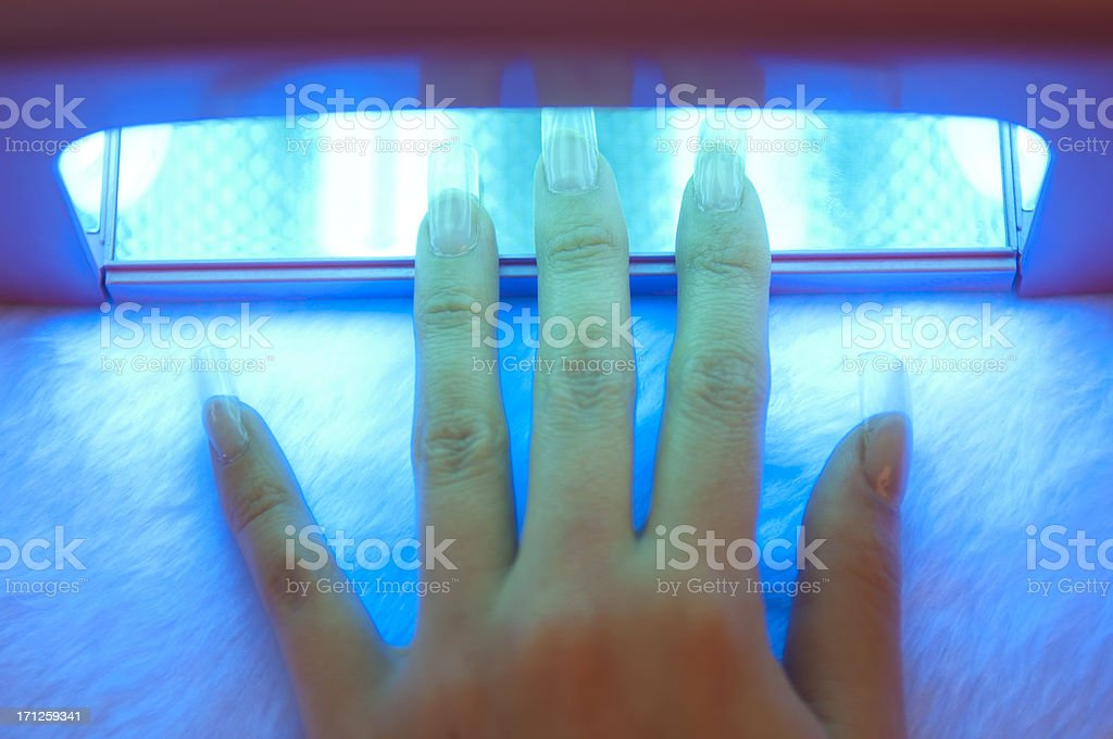 Fingers under UV Nail Dryer stock photo