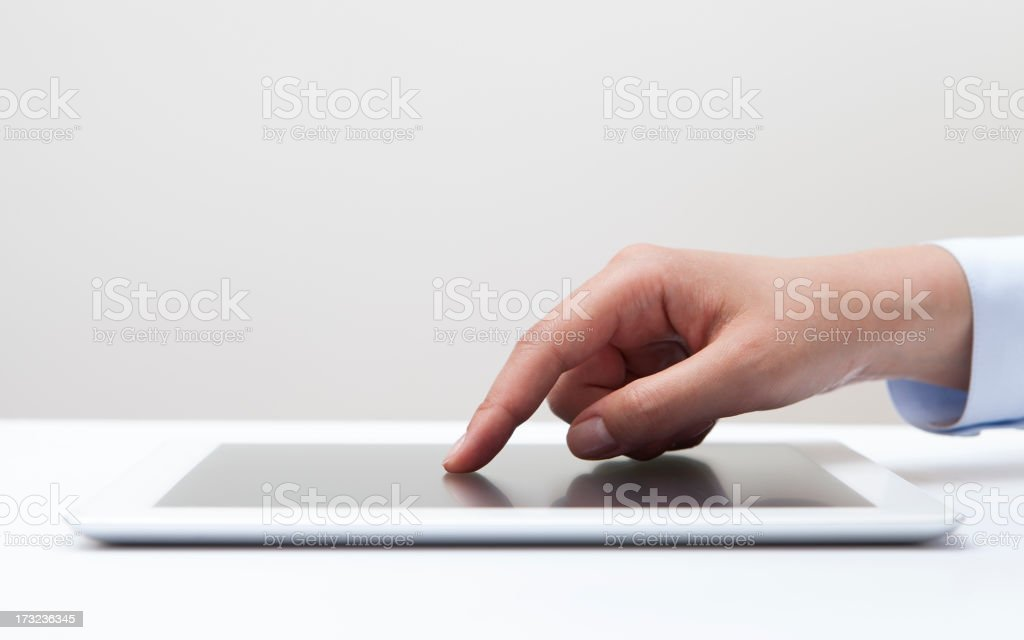 A fingertip touching the screen of a tablet royalty-free stock photo