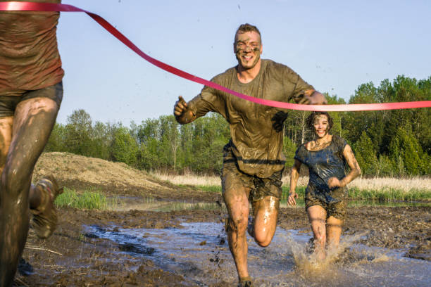 Finish Line Three young adult athletes are about to cross the finish line after an extreme challenge of running through mud outdoors. mud run stock pictures, royalty-free photos & images