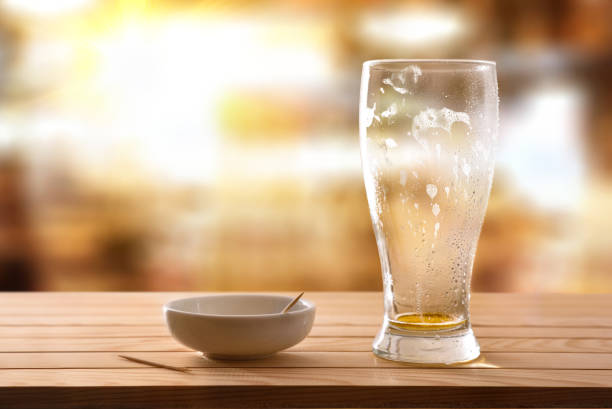 Finished drinking beer glass and empty snack container stock photo
