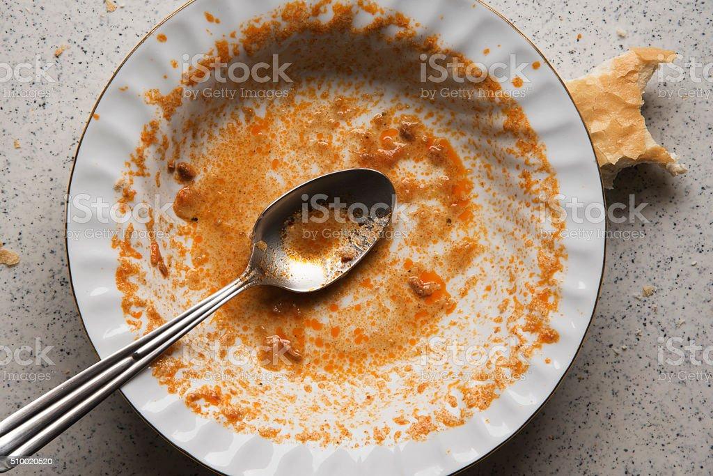 Ist Essen auf einem schmutzigen Teller mit Löffel – Foto