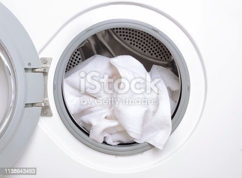 Housekeeper taking out clean clothes from washing machine,closeup
