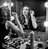 Fashion model doing make-up in front of mirror