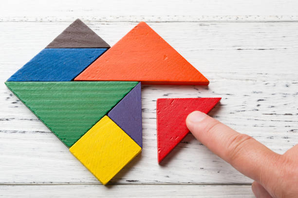 finishing the last bit of wooden tangram in heart shape - puzzles stock photos and pictures