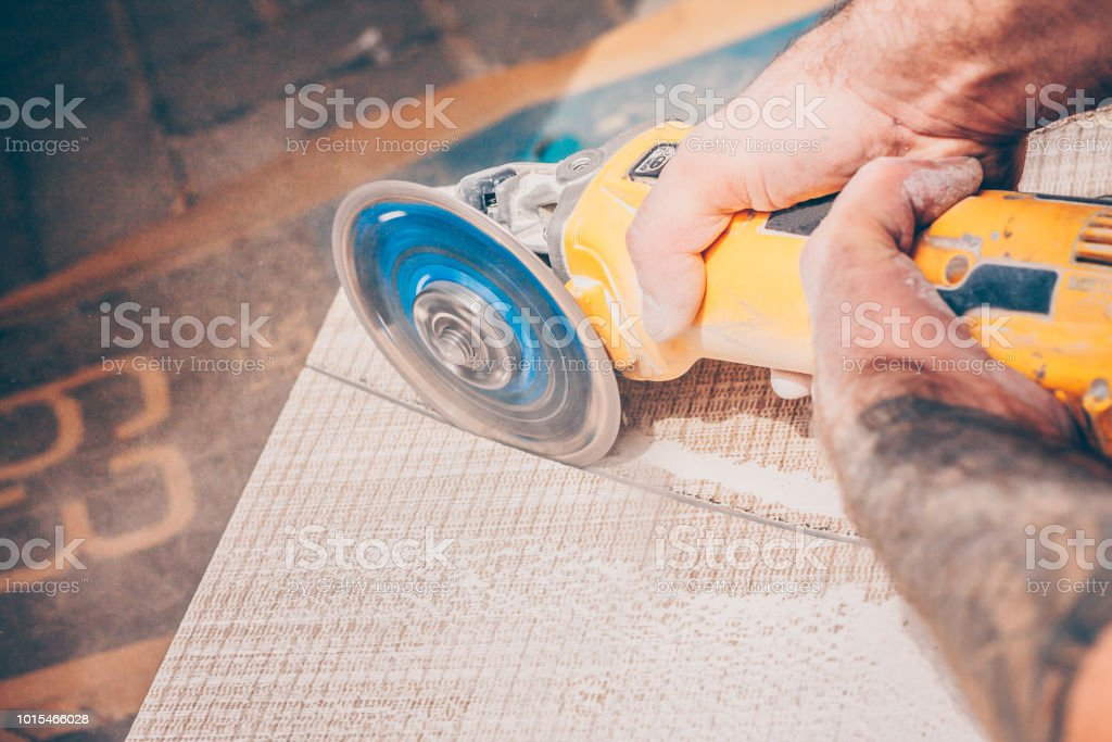 Finishing works - the tiler professionally and qualitatively cuts the tile with an angular grinder stock photo