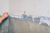 finishing works - the worker makes a marking with chalk with the help of a padded cord on the wall