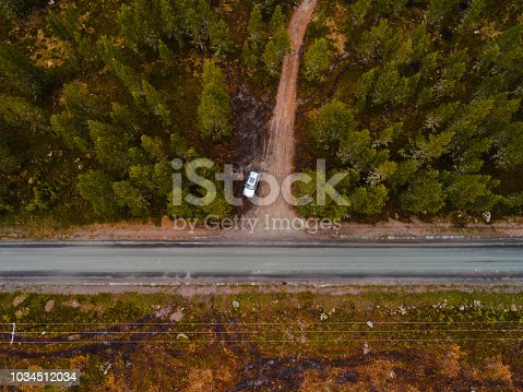 Finland, aerial view of a car parked by the side of the road in the forest of Lapland on a summer or autumn day