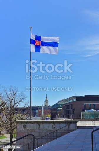 The Finnish State flag is flying on a flagpole of Finnish Parliament building