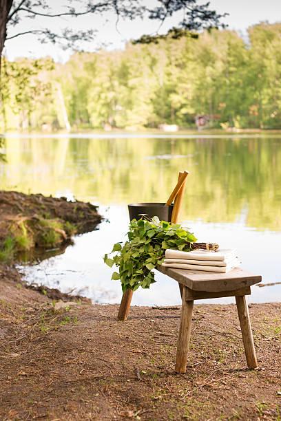 finnische sommer landschaft und sauna objekte auf tisch am see. - sauna textilien stock-fotos und bilder