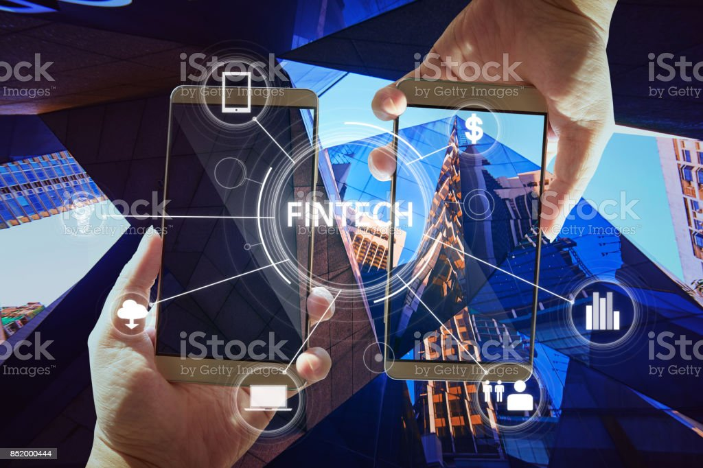 'Fintech' word on digital virtual screen with two businessman hands holding smartphones background. stock photo