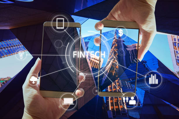 """""""Fintech"""" word on digital virtual screen with two businessman hands holding smartphones background. stock photo"""