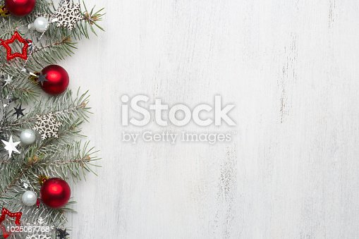 istock Fir branch with Christmas decorations on old wooden shabby background with copy space for text. 1025067768