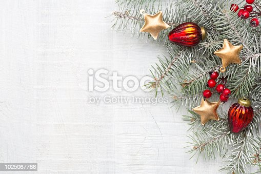 istock Fir branch with Christmas decorations on white rustic wooden background with copy space for text. 1025067786