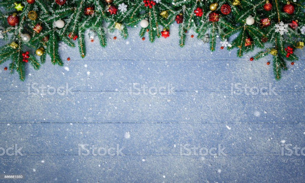 Fir Branches and Christmas Ornament on snowy blue wood plank stock photo