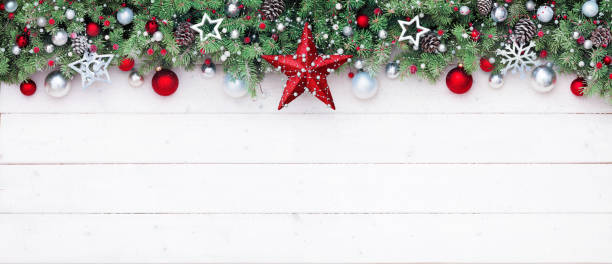 fir branches and decoration on white plank - christmas border - christmas green stock photos and pictures