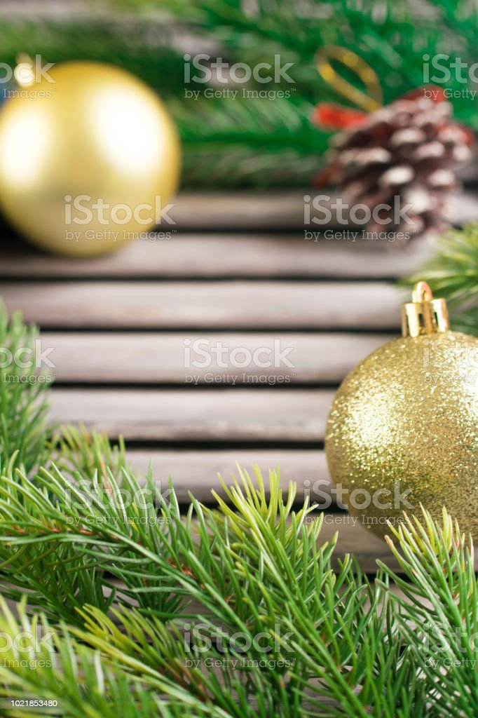 Fir branches and golden balls on wooden rustic desk. Space for text. Christmas. stock photo