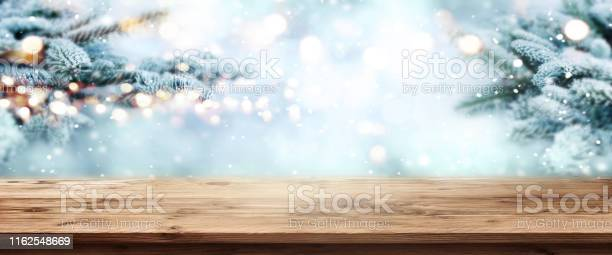 Photo of Fir branches in snow with wooden table