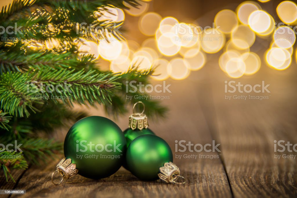 Fir Tree and three green christmas balls on rustic wood and sparkles light backgorund stock photo