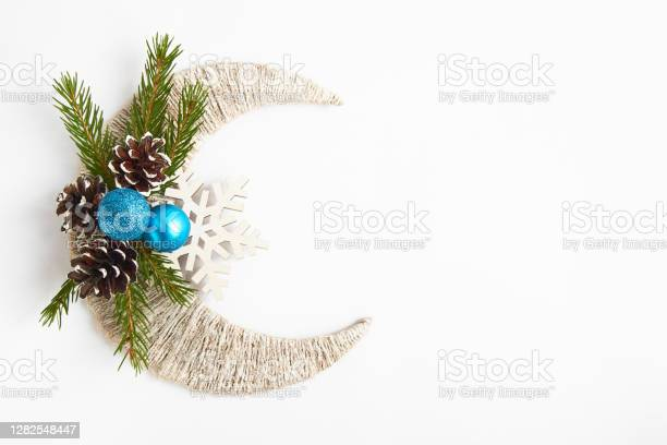 Photo of Fir tree branch, blue balls and pine cones on white crescent and snowflake. Top view with copy space. Flat lay. Christmas background or postcard. New year concept