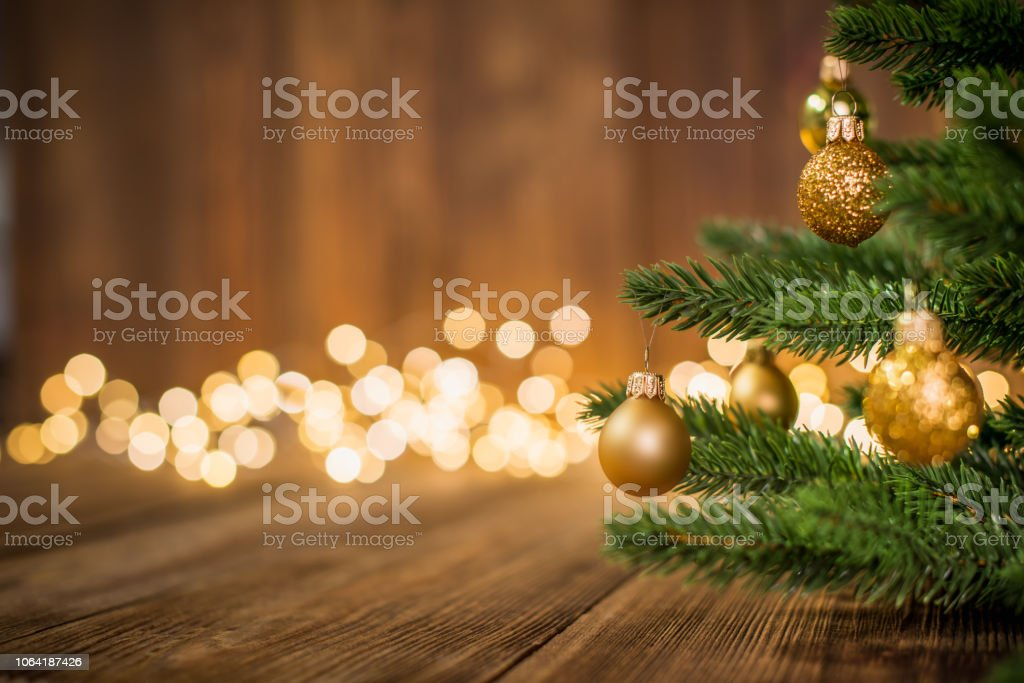 Fir Tree decorated with christmas balls on rustic wood and sparkles light backgorund stock photo