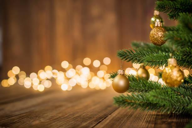 Tanne dekoriert mit Weihnachtskugeln auf rustikalen Holz und funkelt hell backgorund – Foto