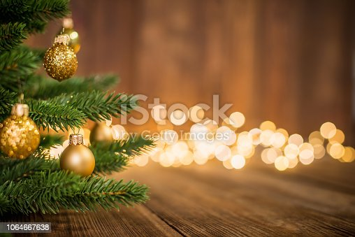 Fir Tree decorated with christmas balls on rustic wood and sparkles / defocused lights on the backgorund. Copy space for creative use.