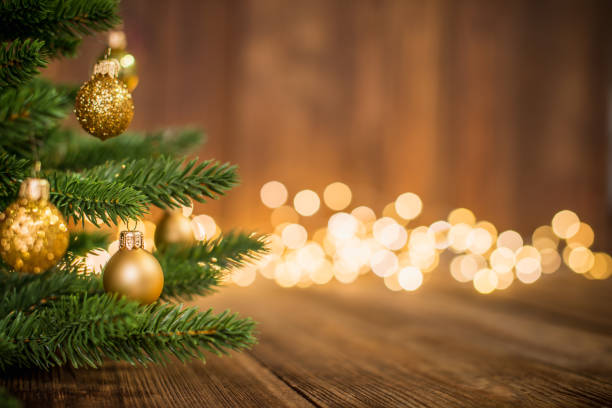 Fir Tree decorated with christmas balls on rustic wood and sparkles light backgorund Fir Tree decorated with christmas balls on rustic wood and sparkles / defocused lights on the backgorund. Copy space for creative use. christmas tree stock pictures, royalty-free photos & images