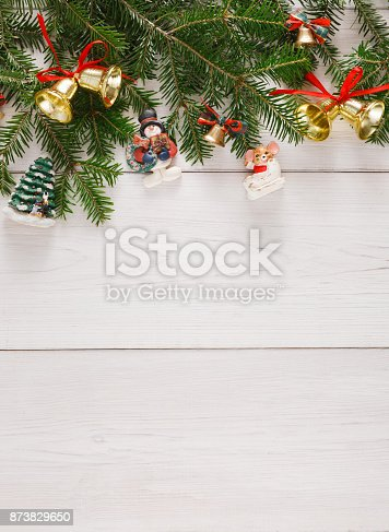 istock Fir tree twigs and new year ornaments border at white wooden background 873829650
