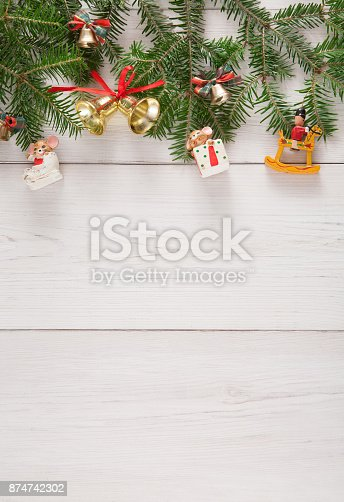 istock Fir tree twigs and new year ornaments border at white wooden background 874742302
