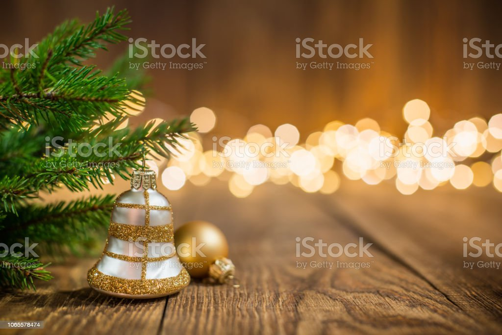 Fir twig and bell bauble on rustic wood and sparkles light backgorund stock photo