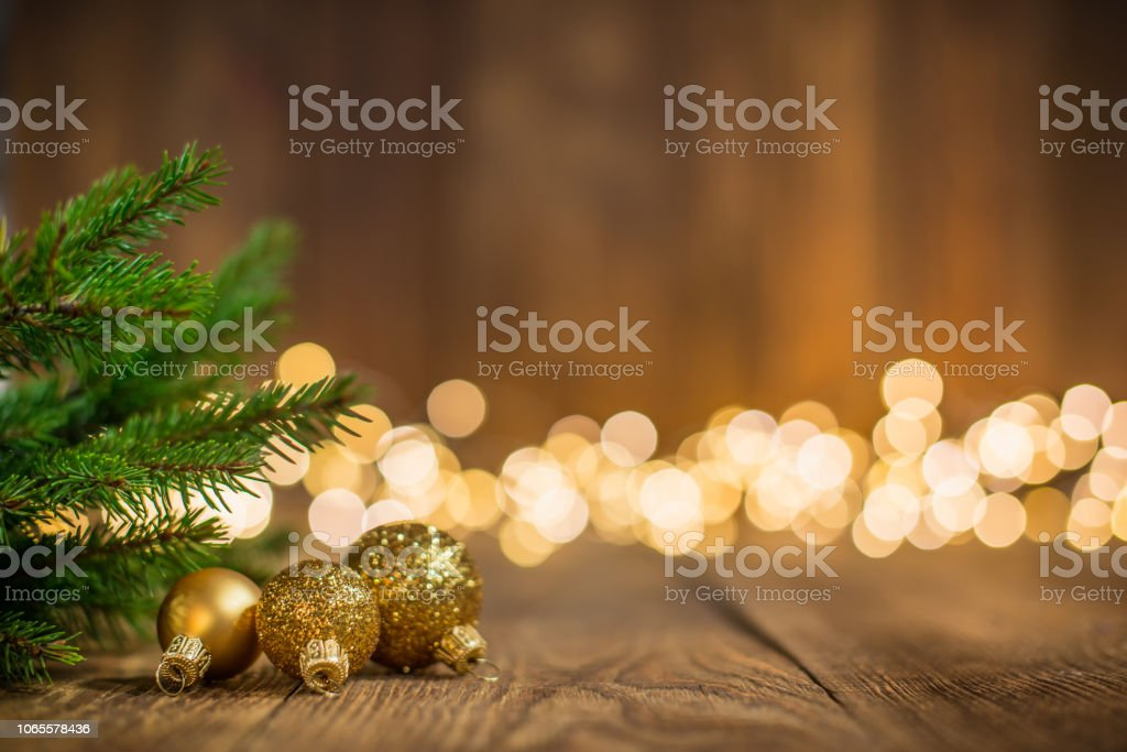Fir twig and christmas ornaments on rustic wood and sparkles light backgorund stock photo