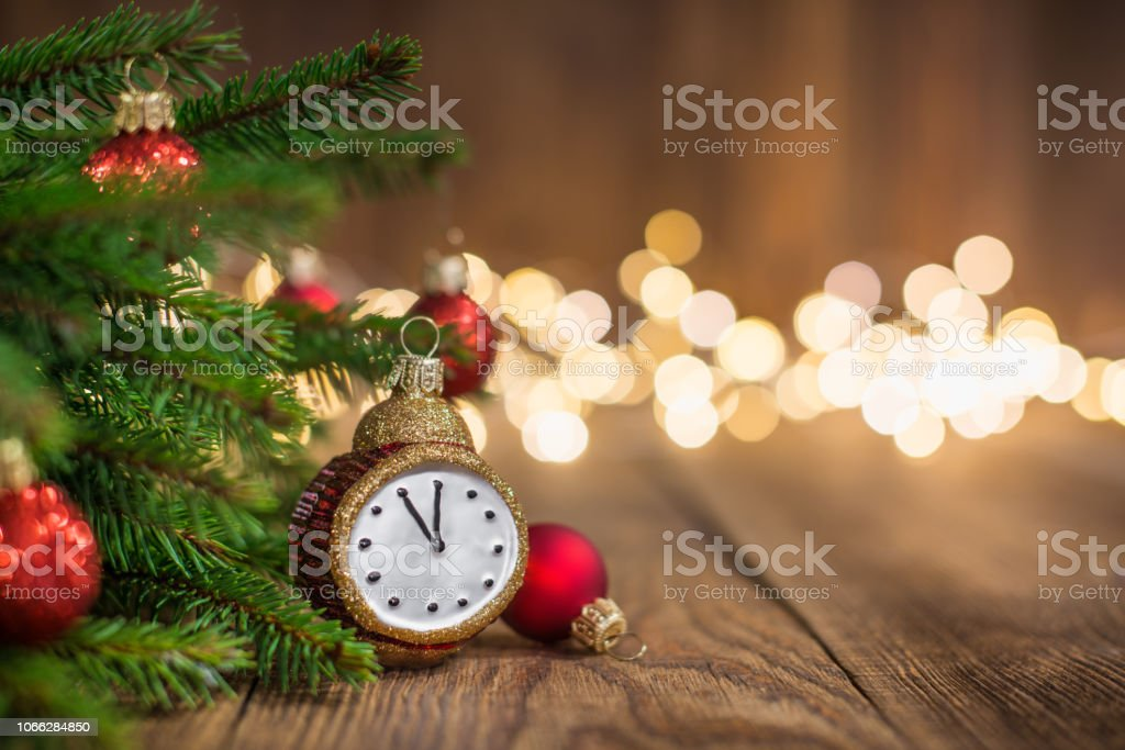 Fir twig and clock styled christmas baubles on rustic wood and sparkles light backgorund stock photo