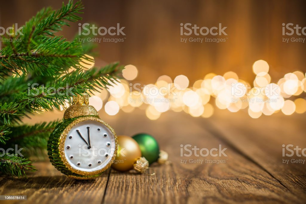 Fir twig and clock styled christmas ornament on rustic wood and sparkles light backgorund stock photo