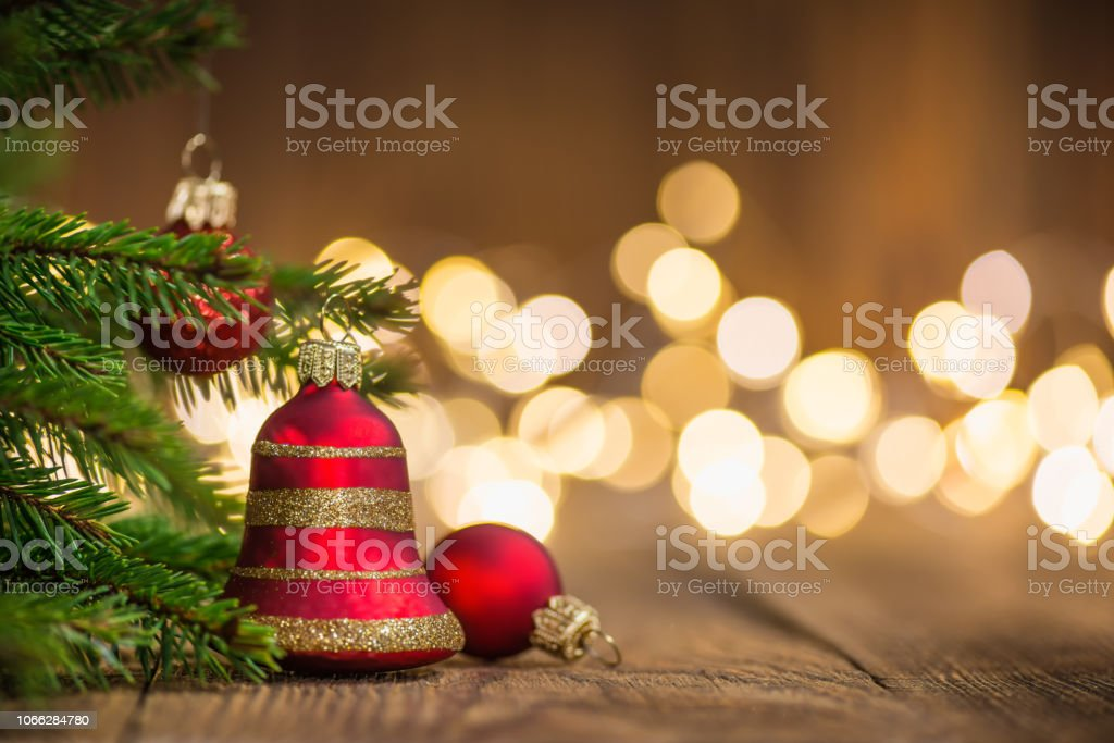 Fir twig and red bell bauble on rustic wood and sparkles light backgorund stock photo