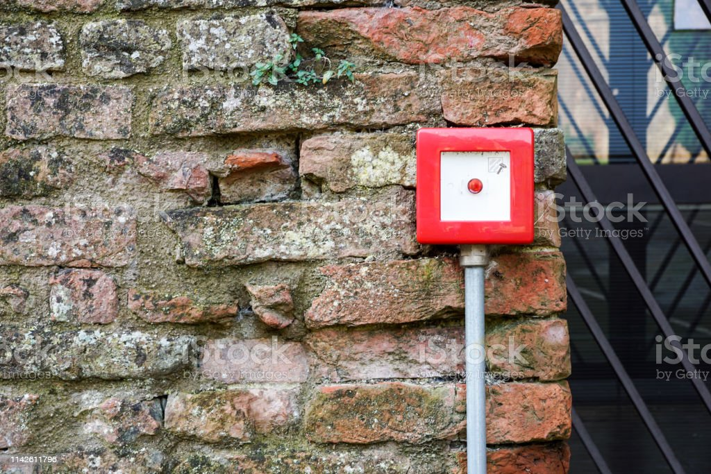 Fire alarm box on white cement wall for security warning alert, push...