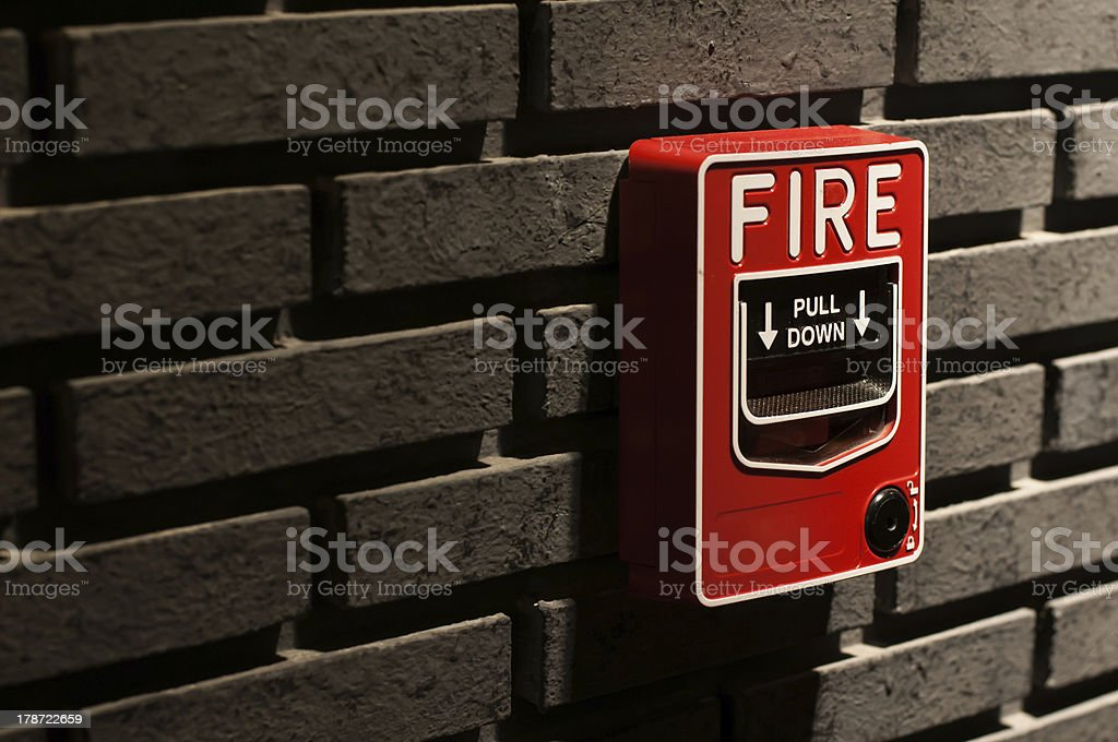 A fire alarm call point box on a brick wall stock photo