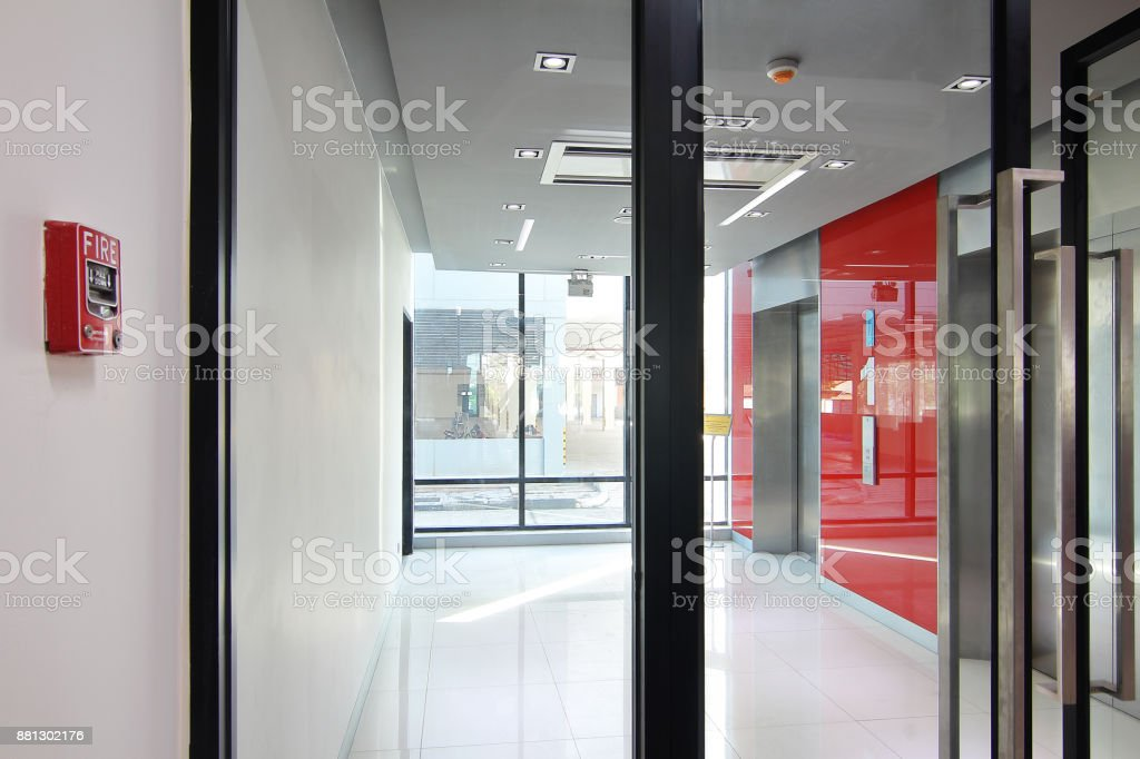 Fire alarm near first  floor elevator and emergency exit of the building stock photo