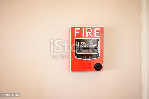 A wall-mounted fire alarm switch with text and braille instructions.