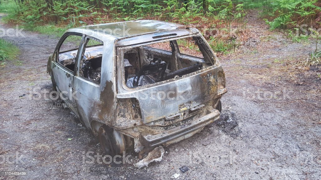 fire and rusty car abandoned along the way in forest road stock photo