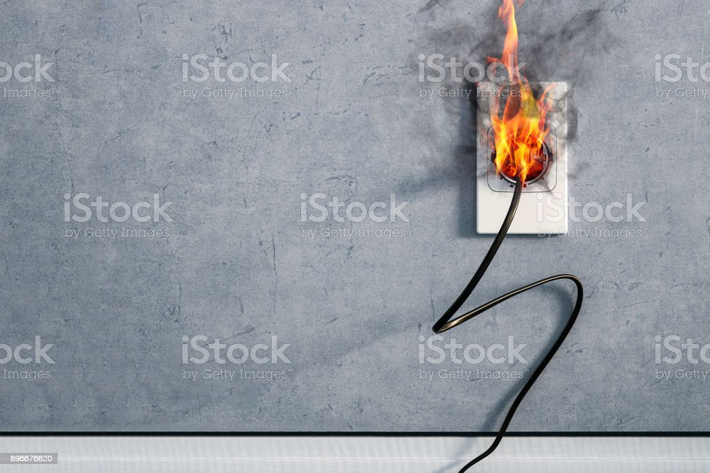 fire and smoke on electric wire plug in indoor, electric short circuit causing fire on plug socket stock photo