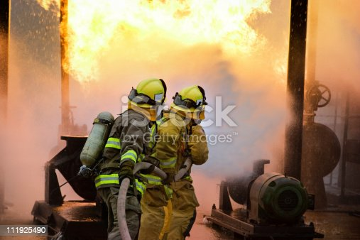 Three firefighters advance with a hose line.