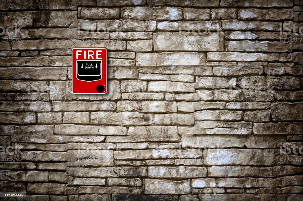 fire break glass fire alarm on old grunge wall