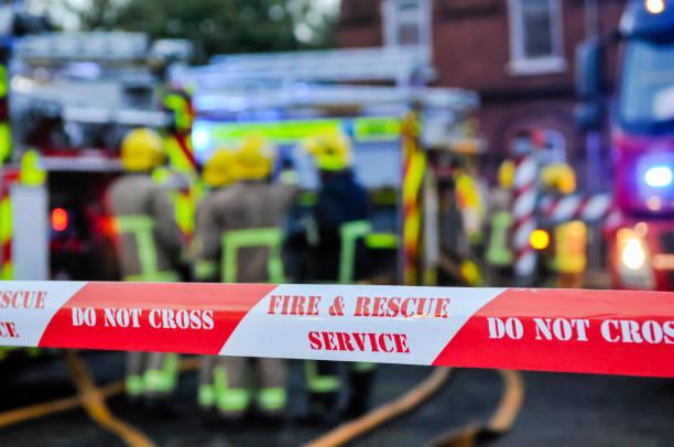 Die Feuerwehr platziert Absperrband um eine mutmaßliche Brandstiftungsszene, um die Menschen zu schützen und Beweise zu bewahren. – Foto