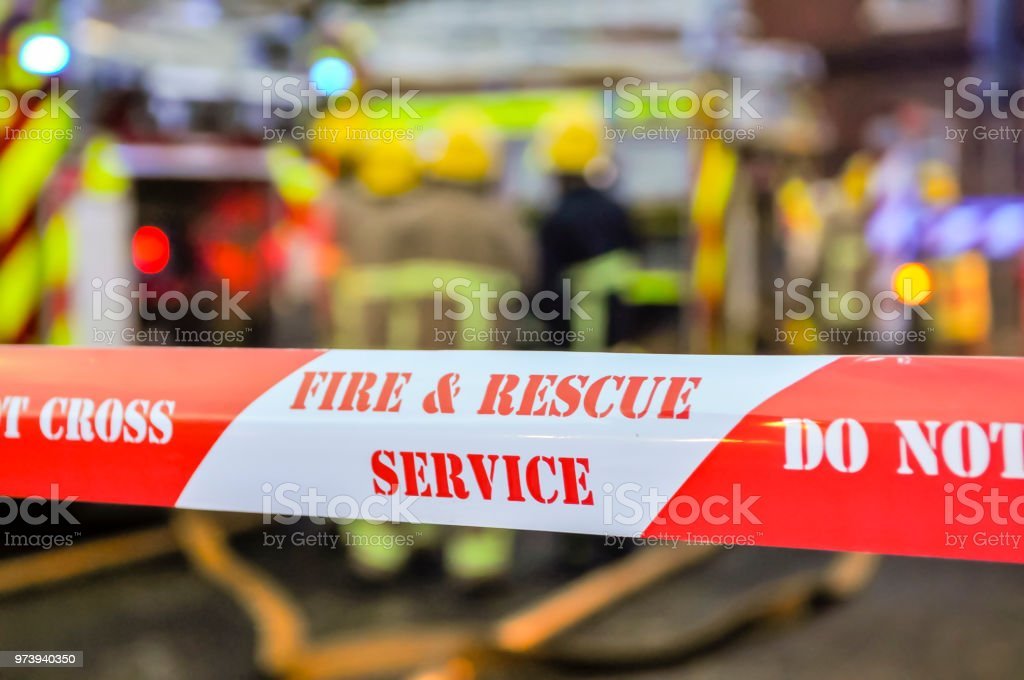 Feuerwehr legen Cordon Maßband um eine vermutete Brandstiftung Szene Menschen schützen und bewahren Beweise. – Foto