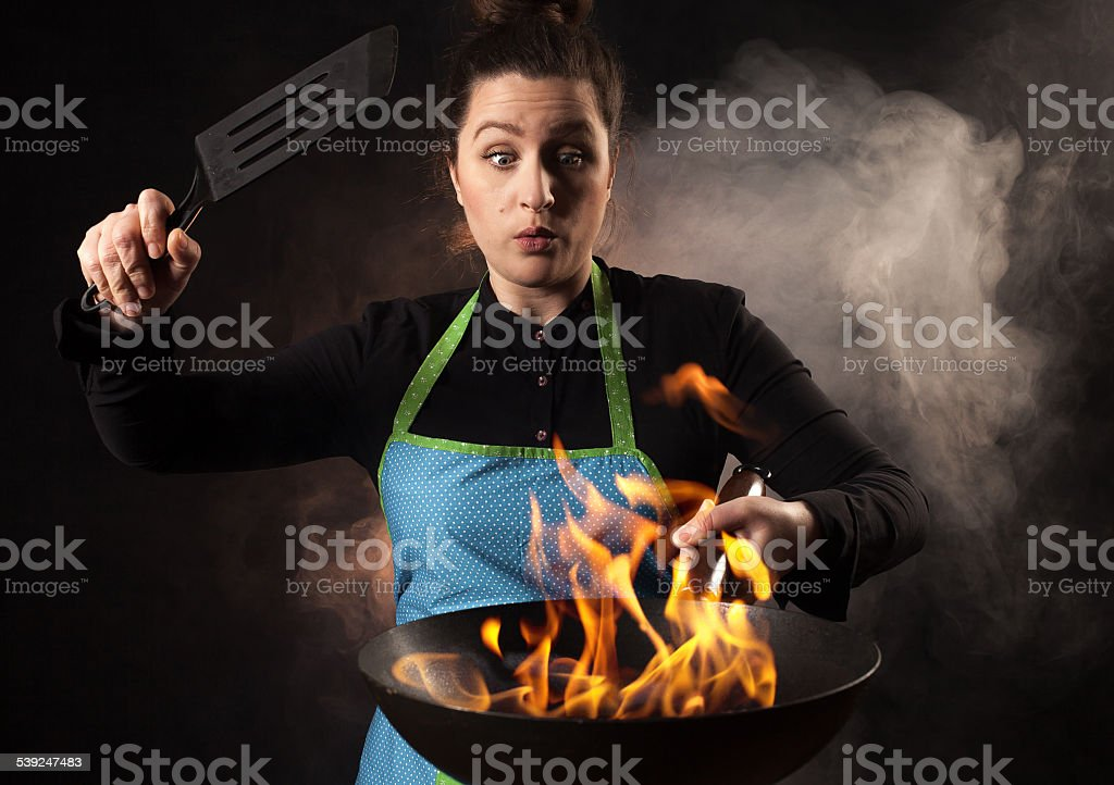 Fire cook woman - wok cooking stock photo